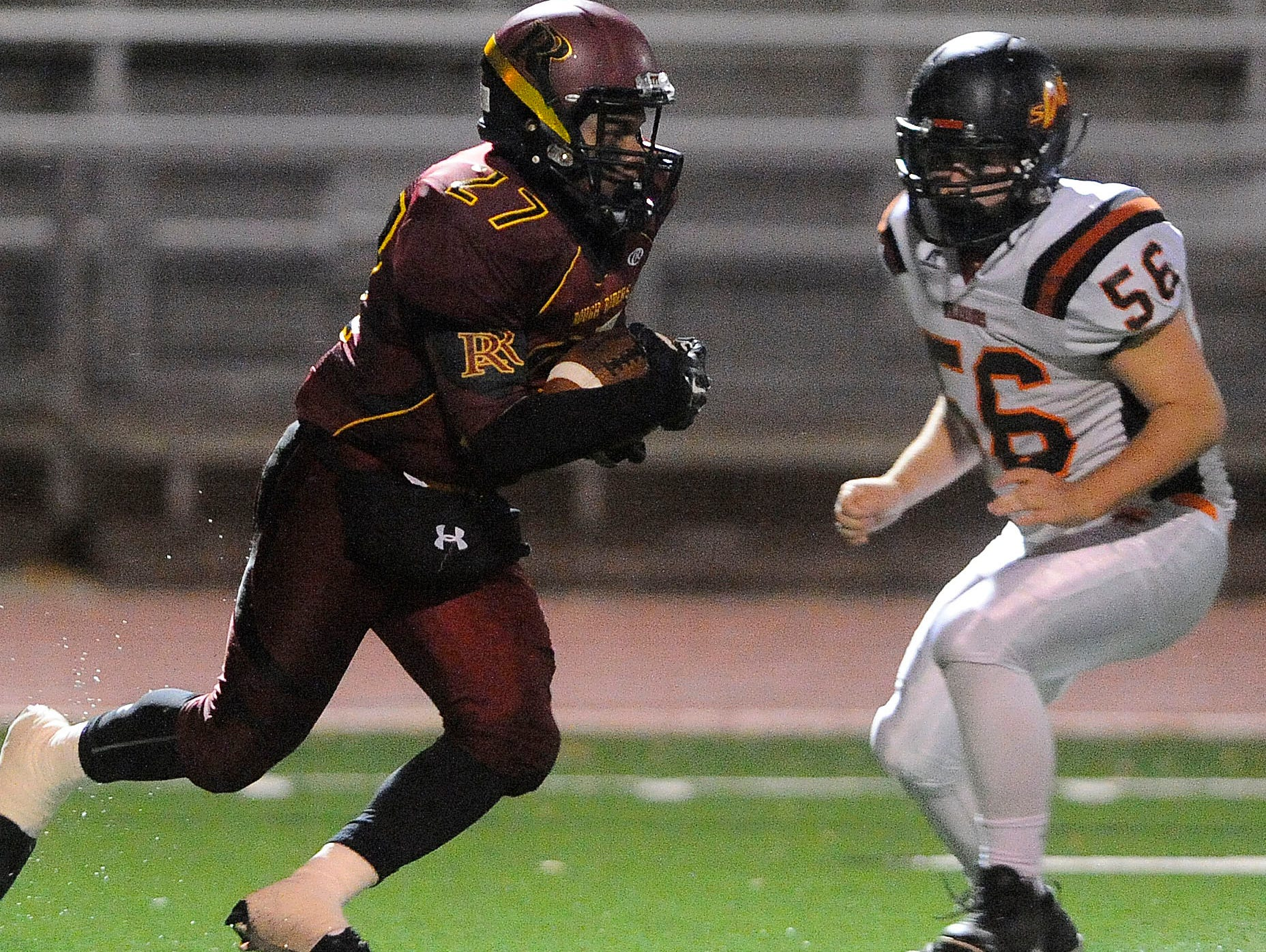 Roosevelt's #27 Tyson Jahn runs down the field against Washington's #56 Thayer Smith during football action at Howard Wood Field in Sioux Falls, S.D., Thursday, Oct. 22, 2015.