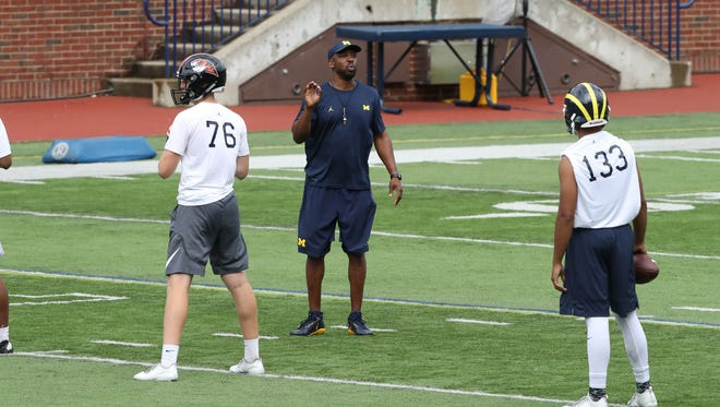 Michigan assistant coach/passing game coordinator Pep Hamilton works with high school quarterback during the Michigan Football Elite Camp on June 23, 2017, at Michigan Stadium.
