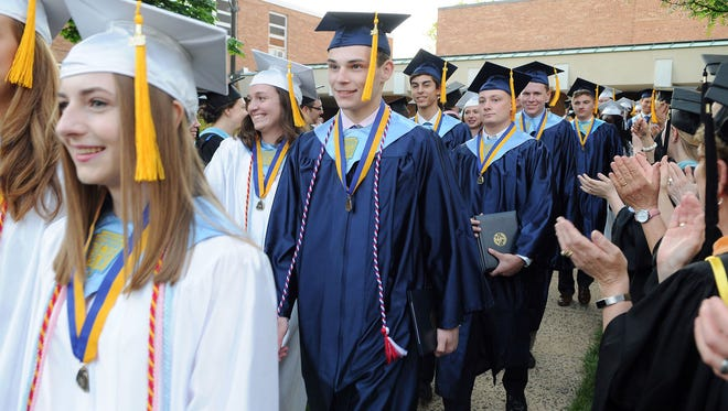 With diplomas in hand, Class of 2018 graduates of Immaculata High School, Somerville, are applauded as they process out of Immaculate Conception Church after the June 1 commencement exercises.