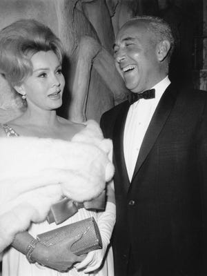 """In this April 10, 1963, file photo, actress Zsa Zsa Gabor and Herbert Hutner arrive for the New York premier of the film """"The Ugly American.""""  Gabor died Sunday, Dec. 18, 2016, of a heart attack at her Bel-Air home, her husband, Prince Frederic von Anhalt, said. She was 99. (AP Photo/Marty Lederhandler, File)"""