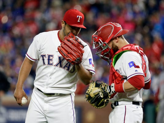 Texas Rangers' Yu Darvish, of Japan, talks with catcher Jonathan Lucroy during the sixth inning of the team's baseball game against the Los Angeles Angels in Arlington, Texas, Saturday, April 29, 2017. (AP Photo/Tony Gutierrez)
