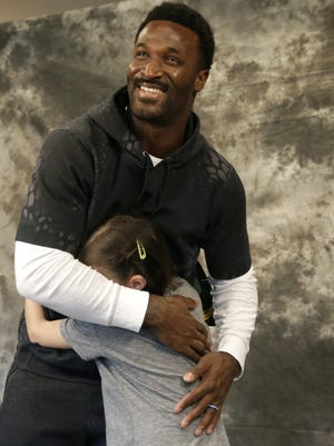 James Jones hugs Maggie Hendrick of Appleton as they come together to sign a special holiday greeting card. Maggie, 8, was diagnosed with leukemia two years ago.