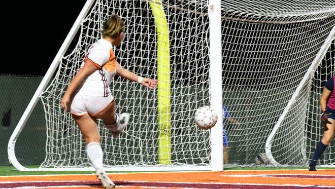 An OUAZ soccer player strikes the ball toward the goal.