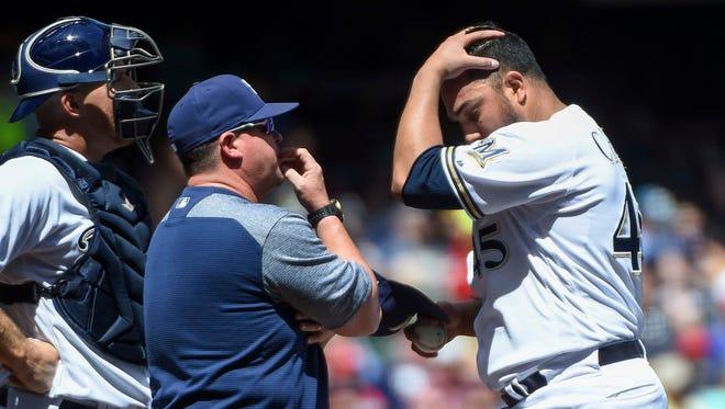 Brewers pitcher Jhoulys Chacin talks to pitching coach Derek Johnson and catcher Erik Kratz in the fourth inning.
