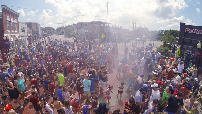 Families cool off under the spray of Brighton Fire's ladder truck after the Brighton Independence Day parade Wednesday, July 4, 2018.