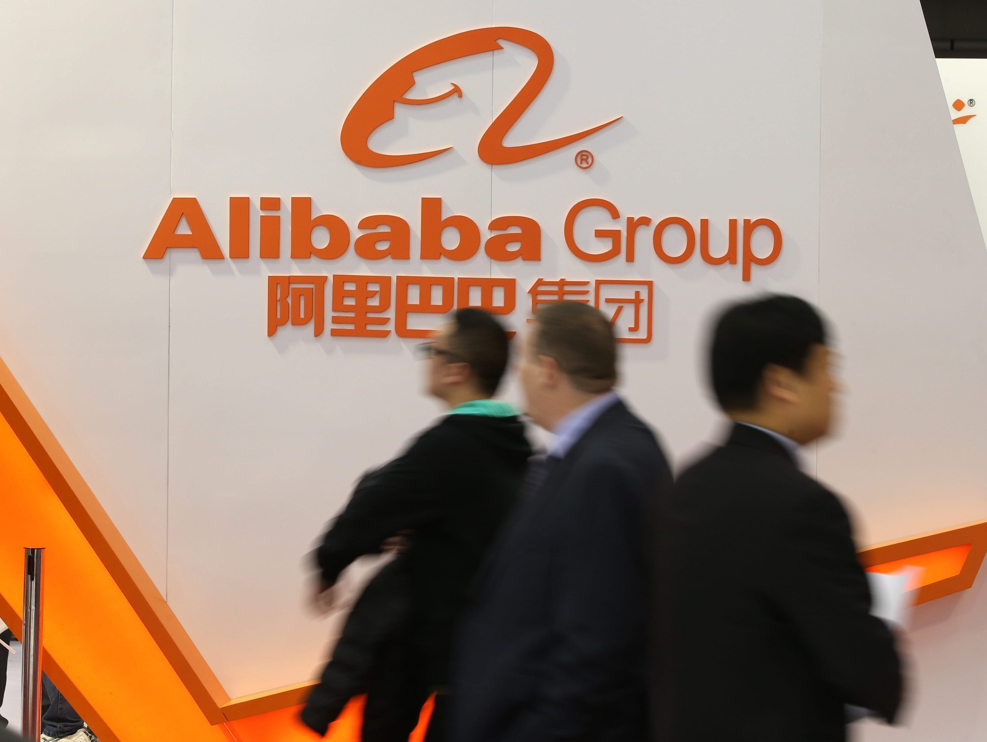 Exhibition visitors walk past the exhibition booth of the Alibaba Group on the opening day of the CeBIT 2015 international computer expo in Hanover, Germany, on March 16, 2015.