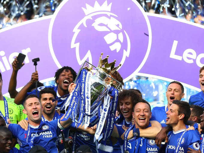 Chelsea players celebrate with the Premier League trophy.