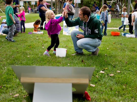 Volunteer Brent Brooks, of St. Clair, gives Peyton Doherty, 3, of Clyde Township, a high-five after playing a bean bag toss game during the Port Huron Township Fall Festival Saturday, September 19, 2015 at Memorial Park.