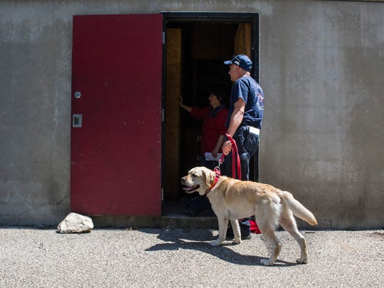 Dean Casealdo and his partner, Dante, an English Labrador retriever, from Clyde, N.C. wait their turn at the base of the EFD fire training tower to go through arson investigation recertification training on Wednesday, June 6.