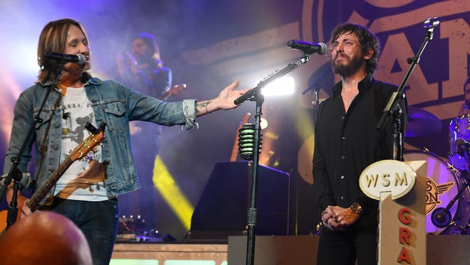 Keith Urban surprises Chris Janson with an invitation to join the Grand Ole Opry during Janson's concert at the Ryman Auditorium on Monday, Feb. 5, 2018 in Nashville.