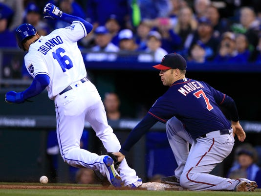 Minnesota Twins first baseman Joe Mauer (7) has trouble with the throw from shortstop Eduardo Escobar on Kansas City Royals' Paulo Orlando (16) during the fifth inning of a baseball game at Kauffman Stadium in Kansas City, Mo., Saturday, April 9, 2016. Minnesota Twins shortstop Eduardo Escobar received an error and Kansas City Royals' Salvador Perez scored from third base on the play. (AP Photo/Orlin Wagner)