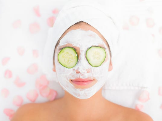 Attractive woman having cucumber on her face