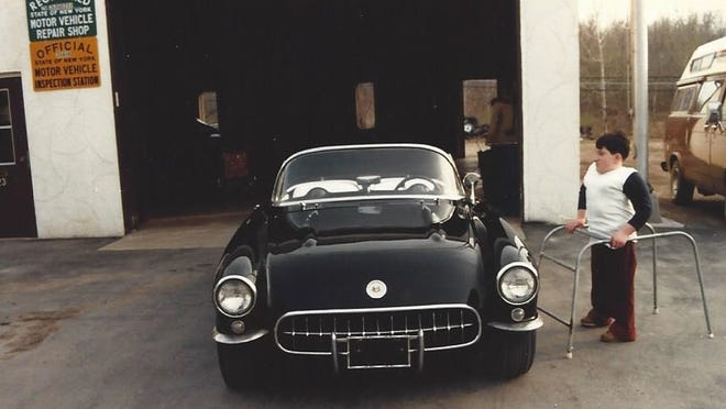 An 11-year-old Tom Turner inspects a 1957 Corvette in front of Turner Automotive in 1981.