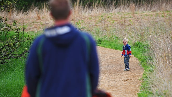 August Jarzynka, 3, looks back at his dad Luke Jarzynka, of Sioux Falls, and brother Blaise, 1, while walking through Good Earth State Park Wednesday, May 17, 2017, southeast of Sioux Falls. A public dedication event will be held on Friday for the park's new visitors center.