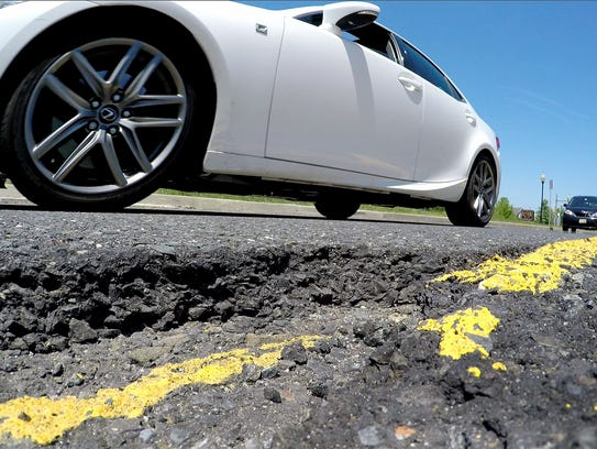 Cars roll past a a pothole outside Brick House Tavern