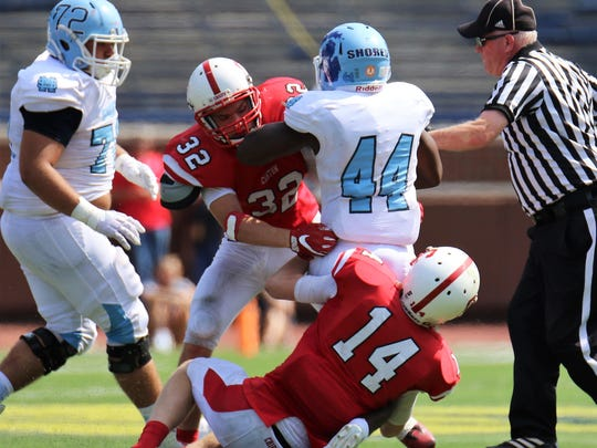 Canton's Aaron Garbarino (32) and Chase Meredith (14) team up to tackle Mona Shores running back Sincere Dent (44).