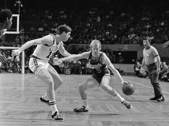 Cincinnati Royals' Tom Van Arsdale dribbles ball as he drives around Boston Celtics' Dave Cowens (18) in 1972.