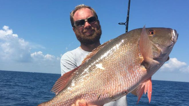 Capt. Brian Godwin, of Lady Stuart party boat out of Hutchinson Island Marriott Marina in Stuart, hoists an 18-pound mutton snapper caught aboard the boat Monday.