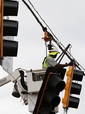 MLGW worker Willie Walker replaces damaged stop lights on Union after a severe thunderstorm knocked out power to most of Memphis Saturday night