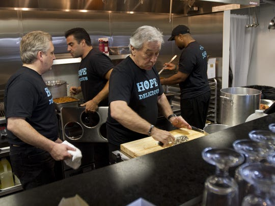 John Bongiovi Sr., father of Jon Bon Jovi,dices onions as he volunteers in the kitchen during the opening of Soul Kitchen in Red Bank. ,
