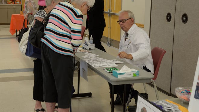 A pharmacist helps a woman evaluate her medications at last year's fall prevention event.