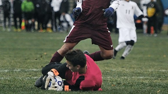 Greece Athena goalie Tyler Graves makes a sliding save on East Hampton's Henry Pillco in November 2014.