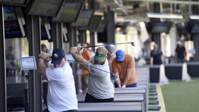 Golfers practice on the opening day of the new Topgolf facility in Augusta, Ga., Friday morning July 3, 2020.