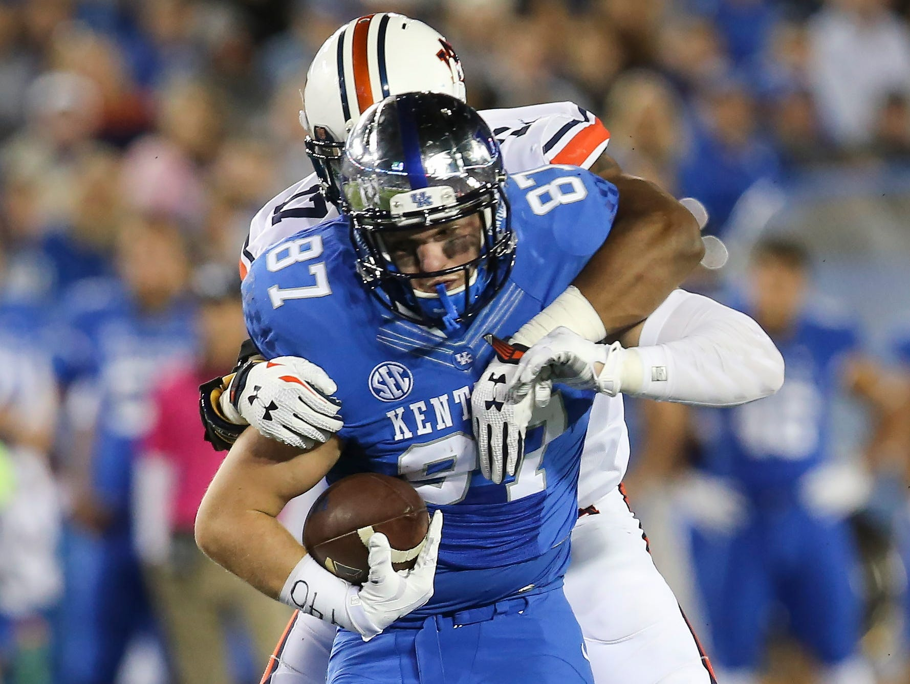 Kentucky tight end C.J. Conrad is tackled by Auburn linebacker Kris Frost during the second half of an NCAA college football game Thursday, Oct. 15, 2015, in Lexington, Ky. Auburn won the game 30-27. Auburn defensive back Johnathan Ford is at bottom.