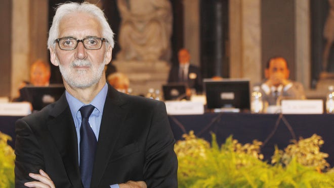 Brian Cookson, of Britain, poses for photographers just after being elected president of the UCI, International Cycling Union, in Florence, Friday.