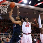 Xavier Musketeers guard Trevon Bluiett (5) reaches for the net as St. John's Red Storm center Yankuba Sima (35) falls off defense during the first half at Carnesecca Arena.