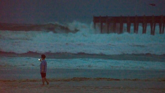 A sightseer takes photos of the high surf as Hurricane Nate approaches in Pensacola Beach during twilight on Saturday, October 7, 2017.
