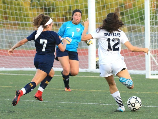Stevenson's Meredith Hage (12) takes aim in front of Farmington defender Emily Pace (7) and goalie Alex Thomas (1).