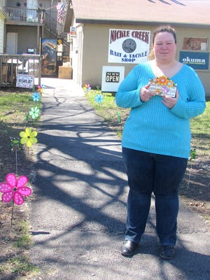Melissa Rinker, co-owner of Nickle Creek Bait & Tackle Shop in Elmira, shows off some of the colorful decorations left by an anonymous donor.