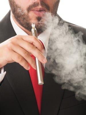 Business man smoking electronic cigarette or e-cig.