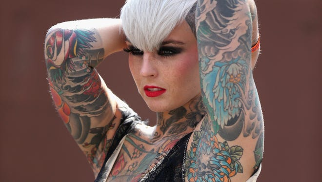 A model poses for photographers at the London Tattoo Convention in 2013.