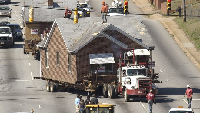 Shoeless Joe Jackson's home was moved from its location on E. Wilburn down Anderson Road to a new site near the Drive baseball stadium. Two sections move together as workers on the roofs help keep the phone and power lines clear on April 4, 2006.