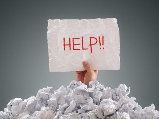 person-buried-under-paper-holding-help-sign-debt_large.jpg
