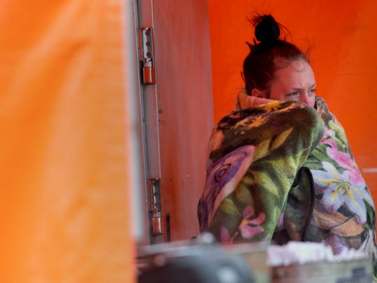 Rachel Lanigra from Syracuse, keeps warm while waiting for customers on the last day of the Lilac Festival.  Lanigra was working at Hammi's BBQ, one of the food concessions at the fest.