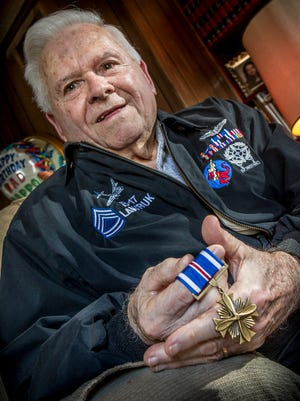 Stanley Lawruk, 90, holds the Distinguished Flying Cross he was awarded as a flight engineer and turret gunner.