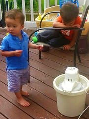 Landon and Braden Cobb stand around an electric ice-cream maker in anticipation of homemade goodness.