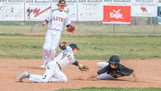 Aztec shortstop Jake Taylor tags out Farmington's Joseph Mihelich during their game on Thursday in Aztec.