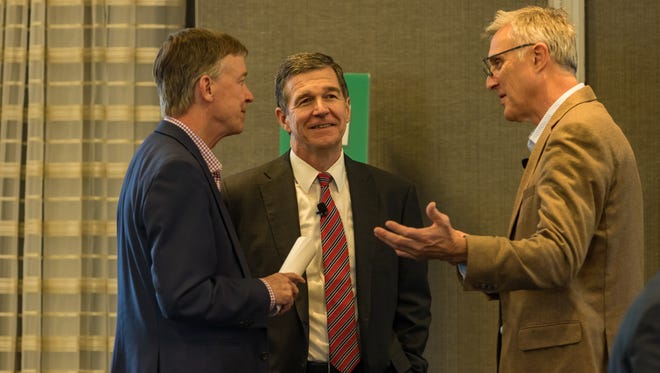 Colorado Gov. John Hickenlooper, left, N.C. Gov. Roy Cooper, and Sylvan Sport president Tom Dempsey, talk after a panel discussion on the outdoor recreation industry Tuesday night at the AC Hotel in Asheville.