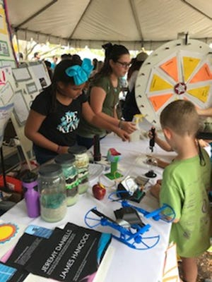 Charity Robinson and Mia Iken discuss their findings on energy with others at the Indian River Lagoon Science Festival.