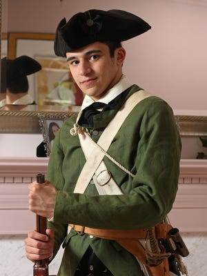 Alex Pena poses in Patriot Militia gear. Pena, 20, is a Revolutionary War re-enactor and in fact, works for both sides: The Colonists and the British. He has been doing this since he was 14. He also speaks to groups and schools about what he does and the history of it.