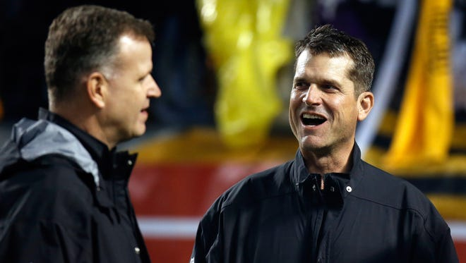 Michigan football coach Jim Harbaugh, right, with Jim Minick, associate athletic director for football, at the Baltimore Ravens' playoff game Jan. 3, 2015.
