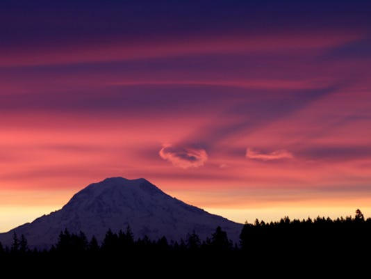 """Red sky in the morning, sailors take warning.""  Western Washington residents may need to heed the warning as the weekend forecast calls for colder temperatures with the possibility of snow.   The photo of Mt Rainier was taken from the Victor Cut-Off road near Allyn.  Low lying clouds cast shadows on the higher cloud ceiling as  as the sun rises behind Washington's iconic peak. (Steve Zugschwerdt/Kitsap Sun)"