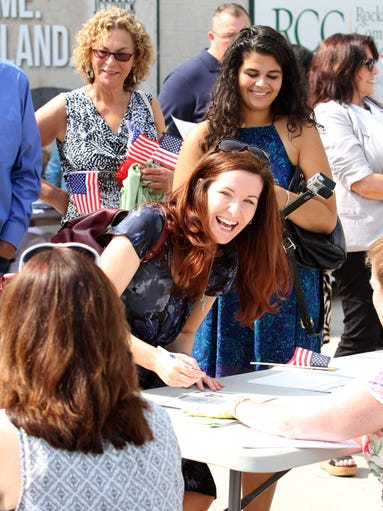 "Jill McNally from Scotland now living in Valley Cottage, signs her naturalization document in front of friends and family, as Rockland County held their naturalization ceremony for the first time at Provident Bank Park in Ramapo, Aug. 1, 2014. 158 people from 47 countries took their oath at the Boulders stadium, home of the ""All American"" sport."