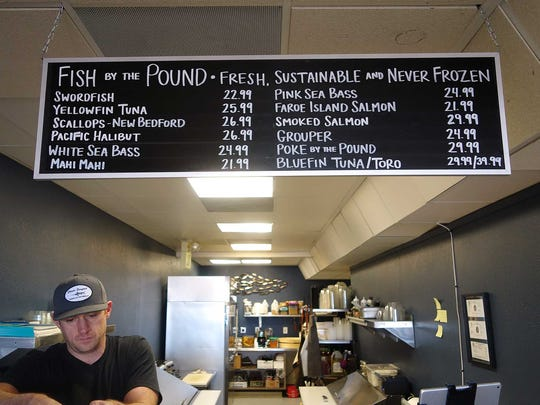 Co-owner Hogan Jamison mans the retail seafood counter