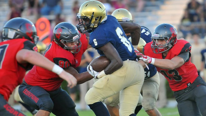 Holy Trinity's Jashaun Corbin is swarmed by the Satellite defense during the preseason meeting.