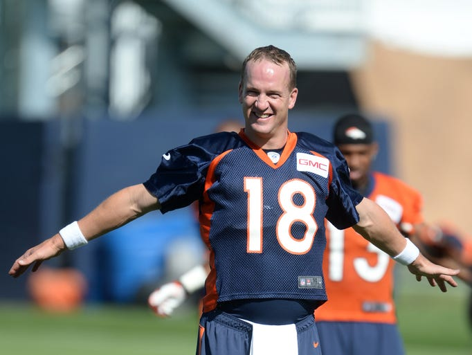 Jul 24, 2014; Dove Valley, CO, USA; Denver Broncos quarterback Peyton Manning (18) warms up during training camp activities at the Broncos training facility